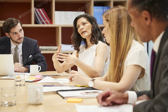 Four people at a business boardroom meeting