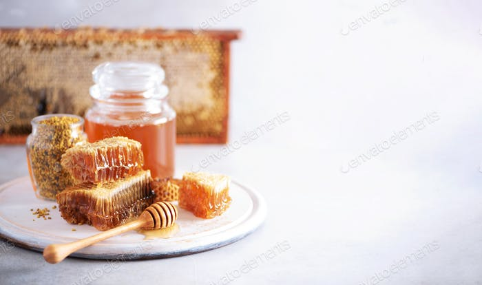 Thumbnail for Bee pollen granules, honey jar with wooden dropper, honeycomb on grey backdrop. Copy space. Autumn