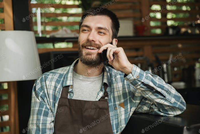 Image of happy waiter boy sitting at the bar and using cellphone