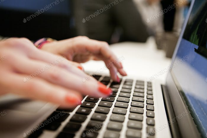 Cropped hands of businesswoman typing on laptop in office