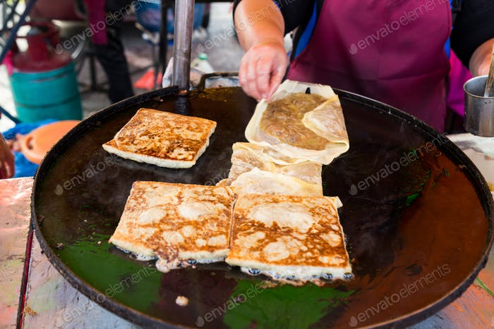 Vendor preparing traditional murtabak cuisine at street bazaar during iftar
