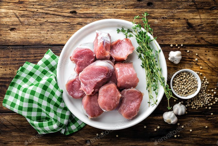 Fresh raw pork tenderloin, chopped meat on dark wooden rustic background, top view