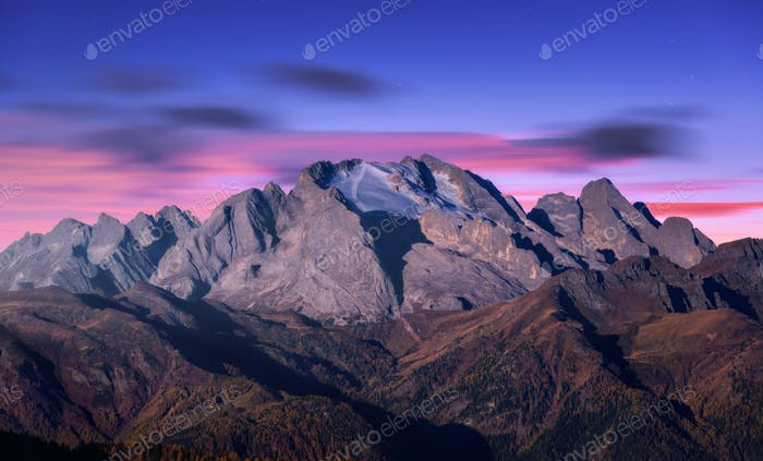 Mountain peak lighted by moonlight in autumn at night