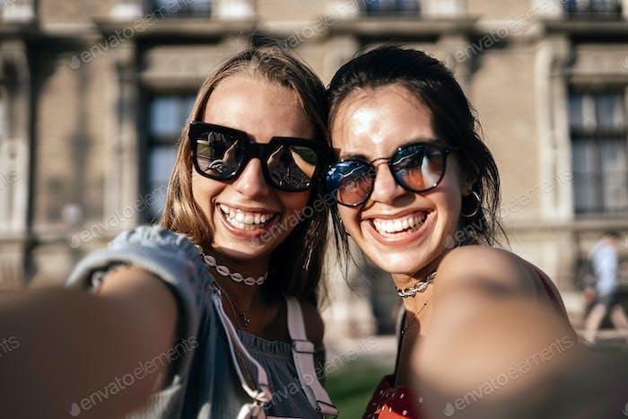 Glückliche junge Frauen in Sonnenbrillen nehmen Selfie