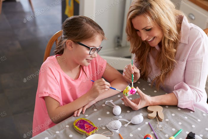 Mother With Daughter Sitting At Table Decorating Eggs For Easter At Home