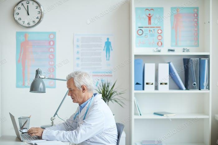 Senior pediatrician working on laptop