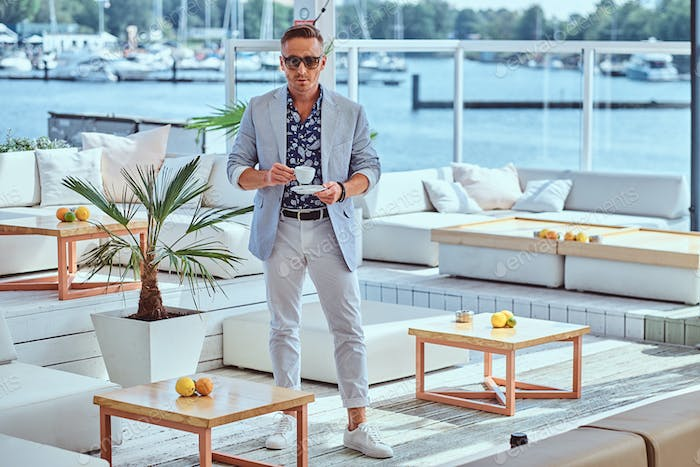 Successful man in modern elegant clothes at outdoor cafe against the background of city wharf.