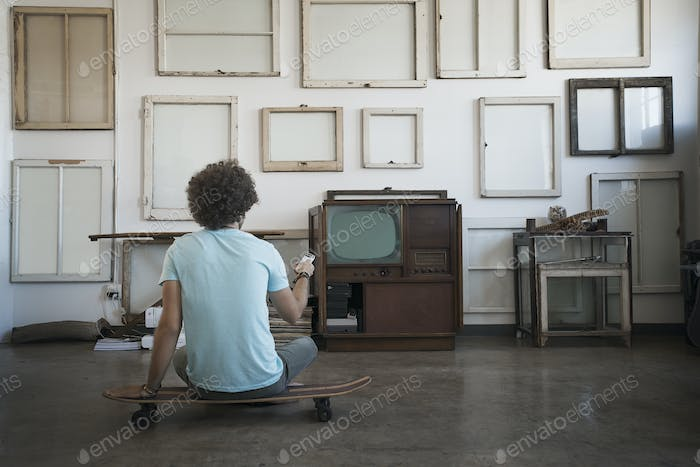 A man sitting on a skateboard looking at a wall of reversed picture frames.