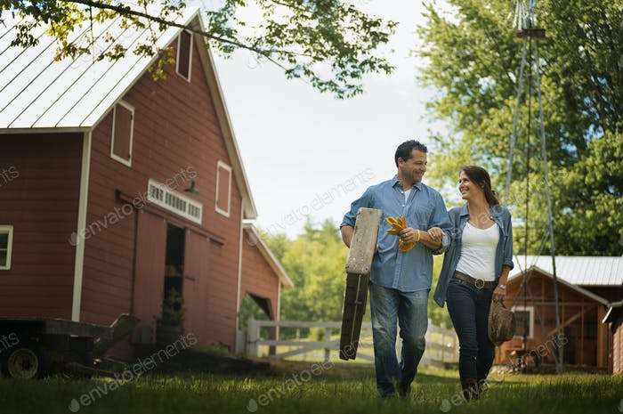 Two people, man and woman in the yard of a traditional farm in the USA.