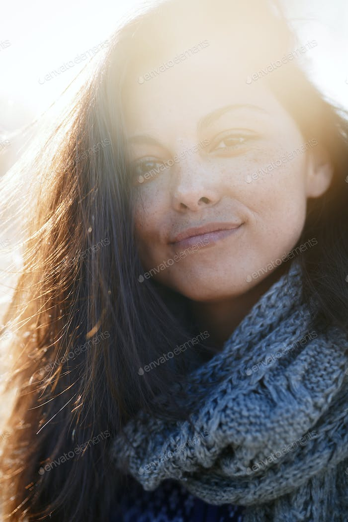 Young adult woman outdoors smiling and looking at camera