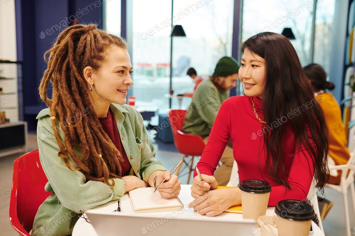 Two young intercultural businesswomen working over presentation together