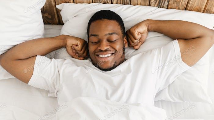 Happy Black Man Waking Up Lying In Bed Indoor, Top-View
