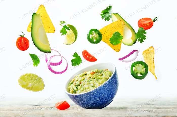 Guacamole with flying corn chips and ingredients to prepare it