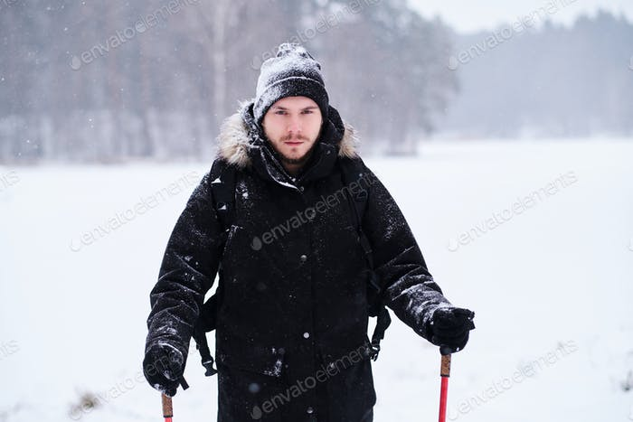 Happy guy doing trekking next to a the snowy forest