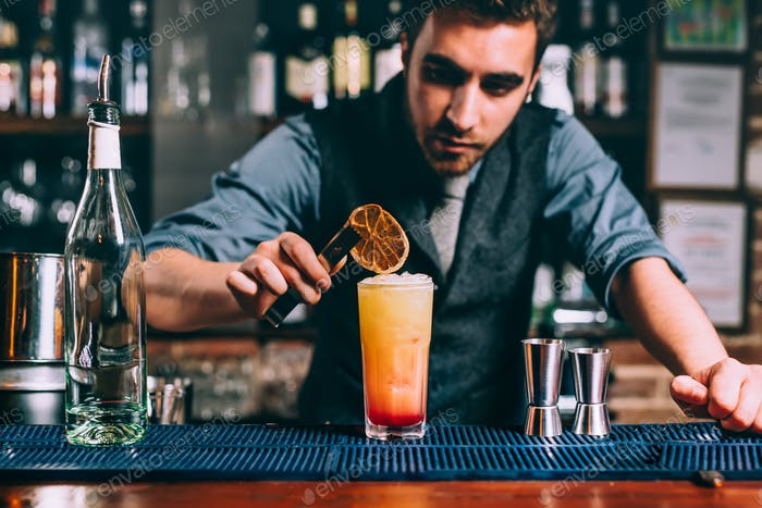 professional bartender preparing summer cocktail with glass and orange
