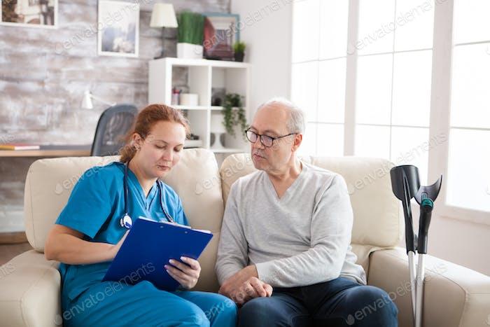 Female doctor in nursing home doing survey