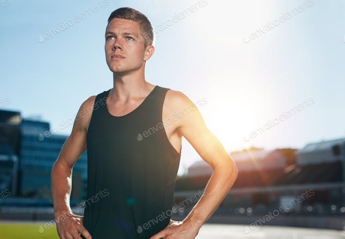 Confident runner on athletics racetrack