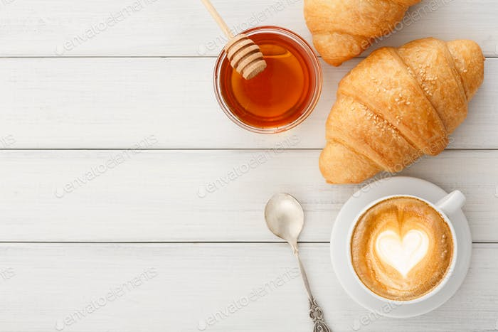 Breakfast with coffee and croissants on white rustic table