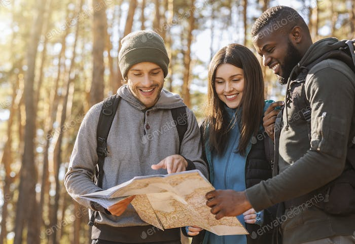 Friends with backpacks looking at map in forest
