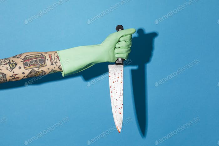 Tattooed hand with a kitchen knife