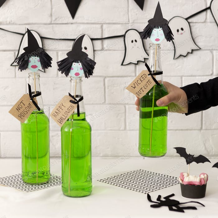 Woman holding halloween cocktail in glass bottle