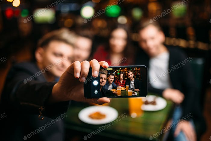Fun Friends macht selfie am Telefon in einer Sportbar