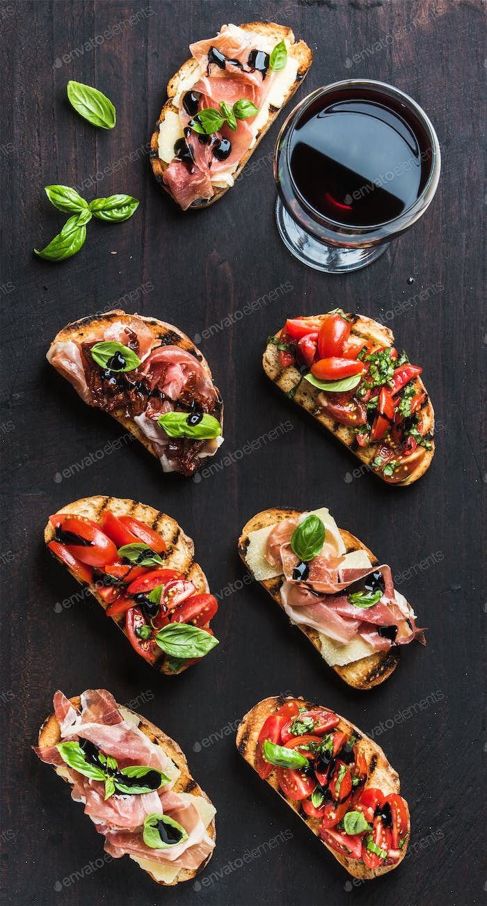 Brushetta set with glass of red wine. Small sandwiches on dark wooden background, top view