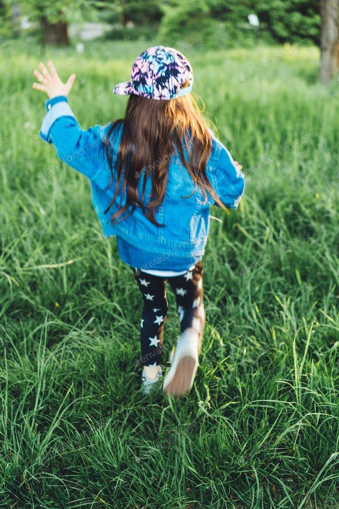 kleines, schönes Mädchen auf dem Rasen