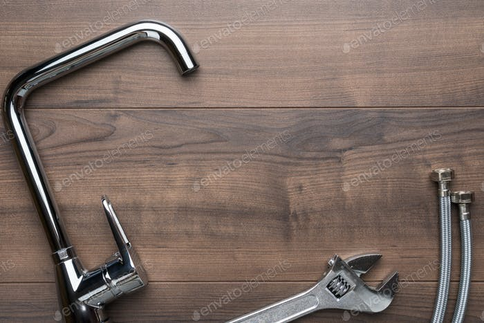 Tap, Wrench, Flexible Hose Connectors Over Wooden Background With Copy Space