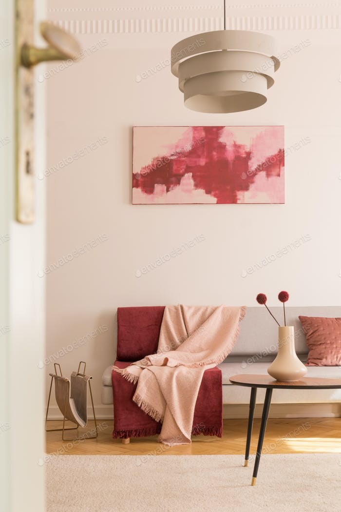 Poster above settee with blankets in loft interior with lamp abo