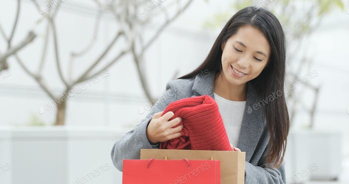Woman look from shopping bag and taking out of the red scarf after shopping