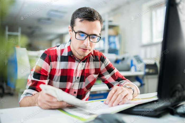 Concentrated designer examining quality of print
