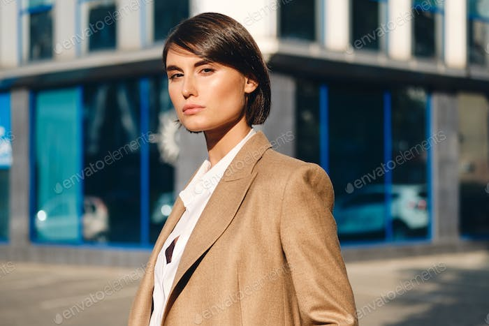 Young beautiful stylish businesswoman confidently looking in camera on street