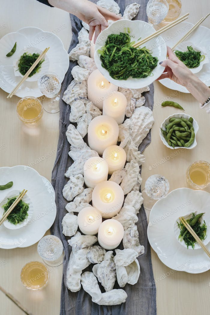 Overhead view of four people sharing a meal, plates of sushi and a table setting for a celebration