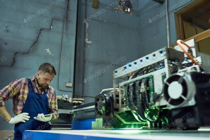 Worker Operating CNC Equipment at Factory