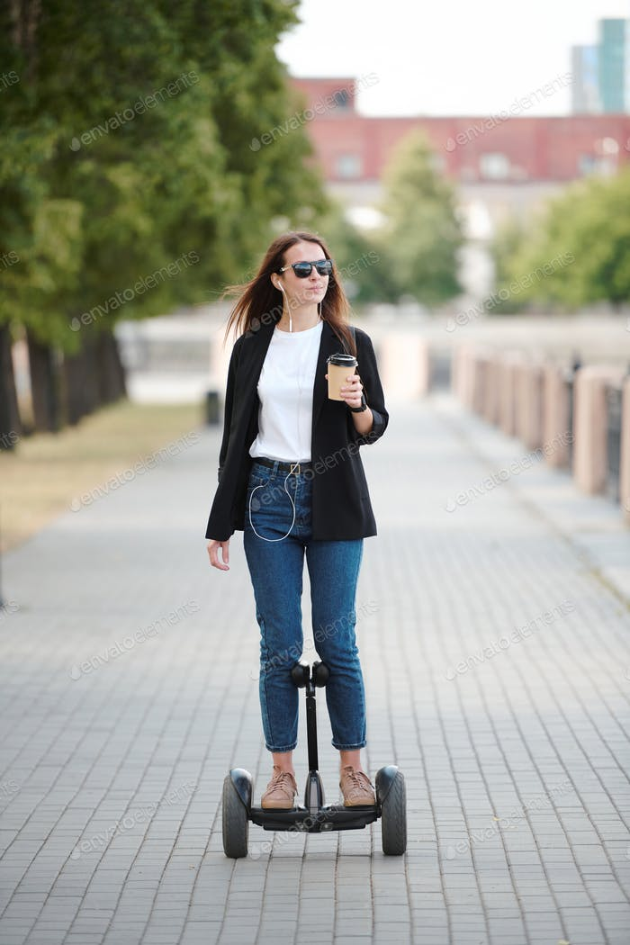 Young female with glass of coffee looking at riverside while riding on gyroscope