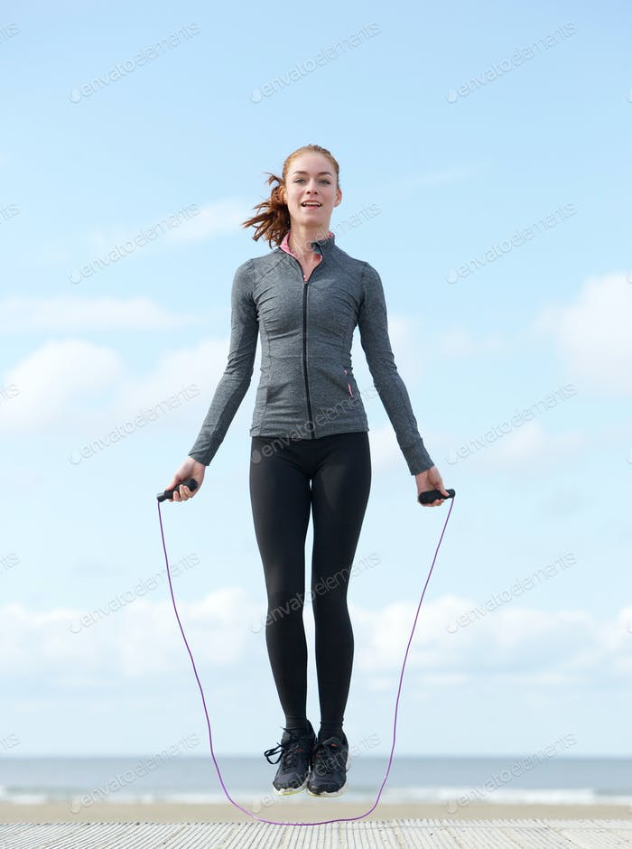 Young woman jumping with skipping rope outdoors