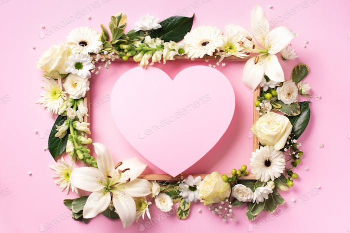 Creative layout with pink flowers, paper heart over punchy pastel background. Top view, flat lay