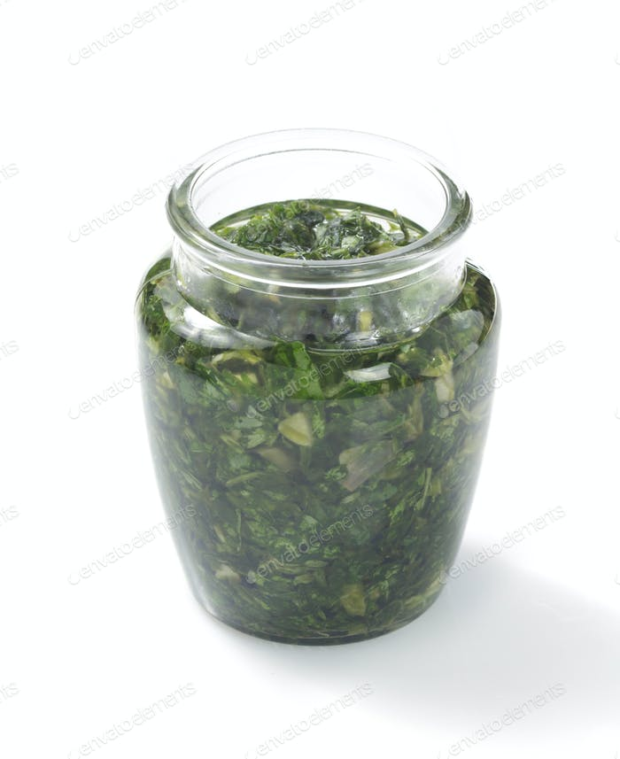 pesto sauce in jar on white