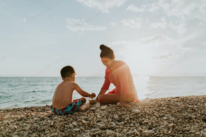 Child playing with stones on beach with his mother at sunset.