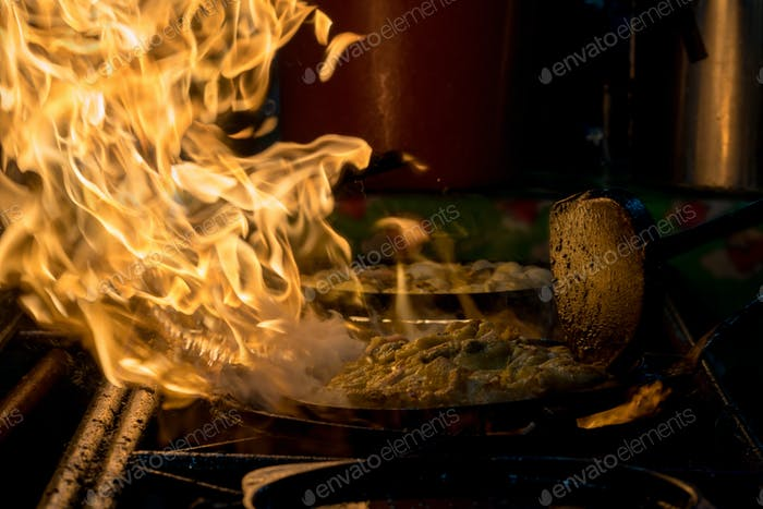 Close up movement hand holding the spade of frying pan cooking the delicious traditional Thai food