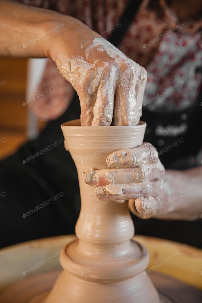 Unrecognizable potter master creating new ceramic jug