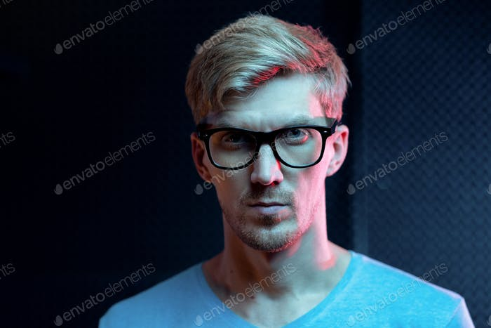 Serious young blond man of Caucasian ethnicity looking at you through eyeglasses