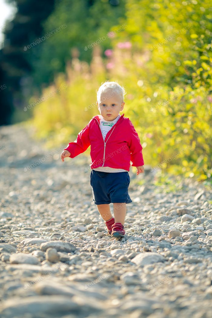 Baby boy hiking on dirt road in forest