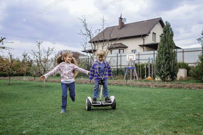 Kind reitet auf selbstausgleichendem Hoverboard auf dem Hinterhof des Ferienhauses, Aktivitäten für Kinder im Freien
