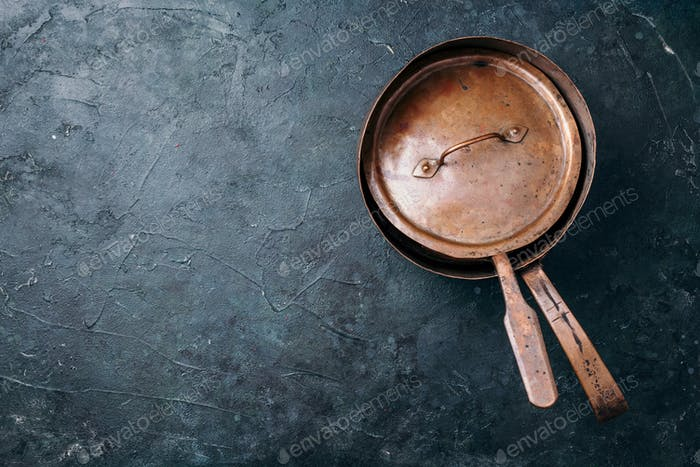 Old vintage copper pots on dark background. Kitchen utensils. Rustic pan. Top view, copy space for