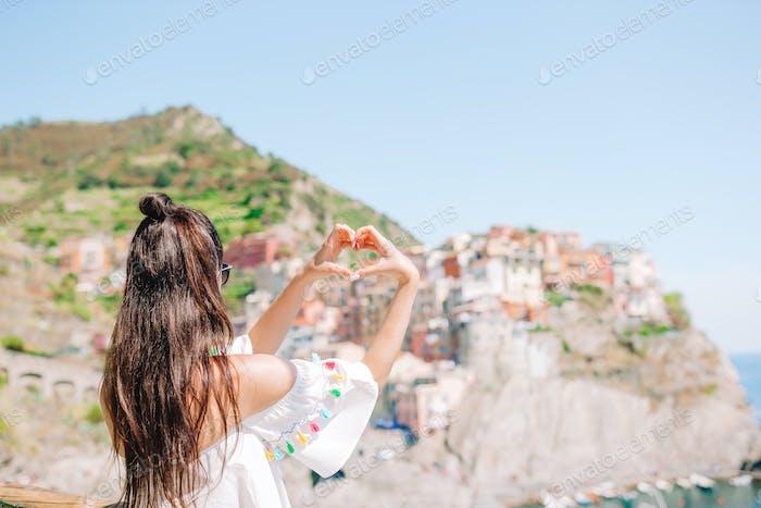 Glückliches Mädchen, das mit den Händen Herzform auf dem alten Küstendorf im Nationalpark Cinque Terre macht