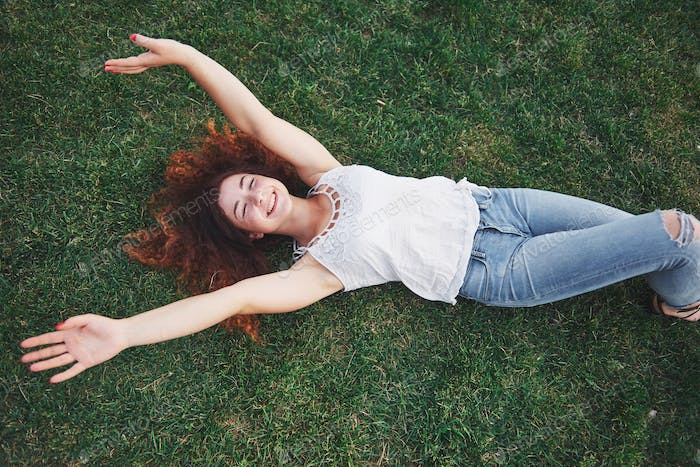 Relaxing girl with red, lying on the grass. Woman relaxes outdoors