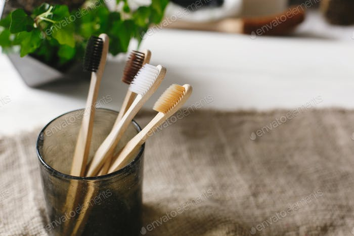 Eco natural bamboo toothbrushes in glass on rustic background