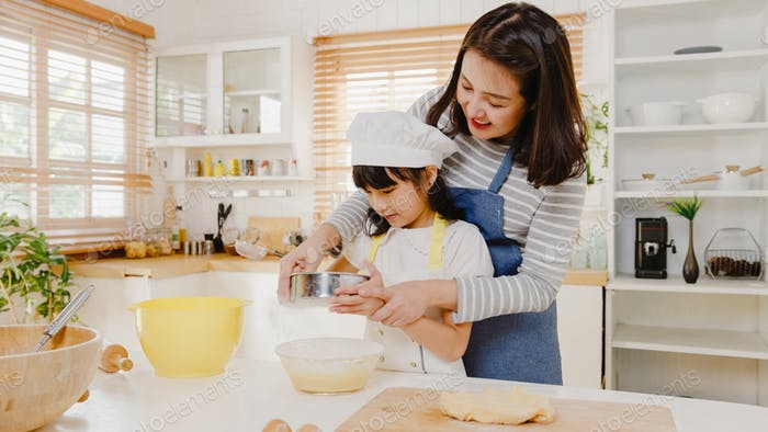 Asian family with preschool kid have fun cooking baking pastry or pie for breakfast meal in kitchen.